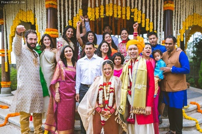 Perfect family picture with right amount of genda phool decor in the backdrop!