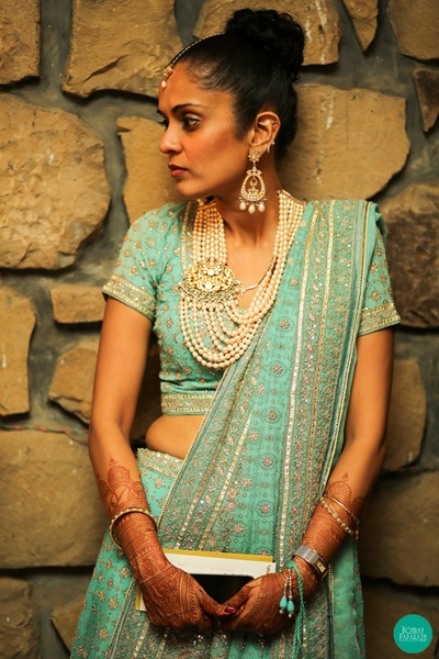 Tiffany blue monotone lehenga styled with multi strand pearled haar featuring a pendant studded with stones and kundan and dangling pearl drop earrings