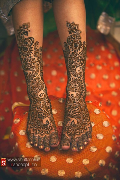 Bride's feet covered in intricately patterned mehendi design
