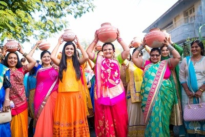 Wedding guests dressed in colorful ethnic outfits for the pooja ceremony held at home
