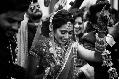 black and white capture of the bride making her way to the mandap
