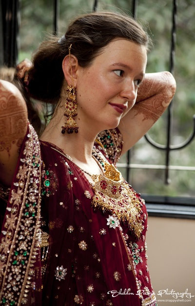 Bride adorned in a traditional maroon embellished lehenga getting ready for her special day