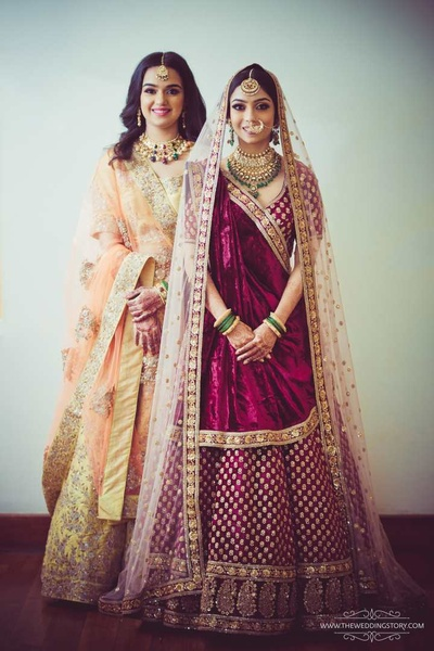 Bride and her sister pose in contrasting colored lehengas for the wedding ceremony