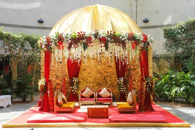 Wedding mandap decorated with red drapes, floral tie backs and clustered floral arrangement
