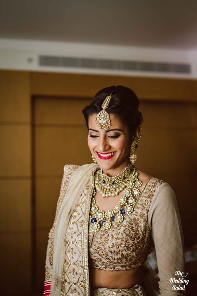 Gold choker and two-strand raanihaar studded with polki and blue sapphire stones styled with matching jhumka earrings