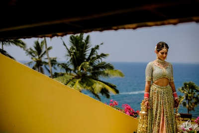 the beautiful bride in a heavily embellished sage green lehenga for her wedding ceremony