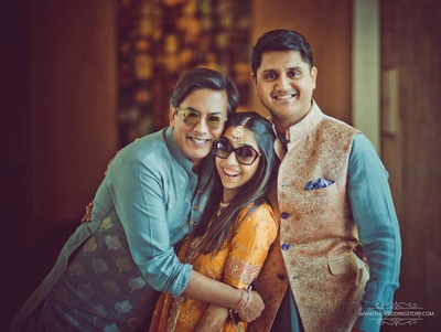 The bride and groom pose with a family member in a candid bridal shot