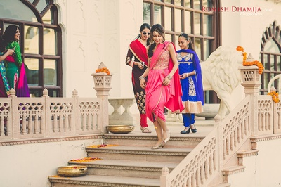 Nanki entering the mehendi venue with her bridesmaids, all colorfully dressed up.