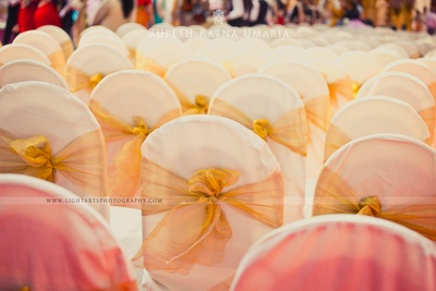 White chair covers with gold tissue tie-backs