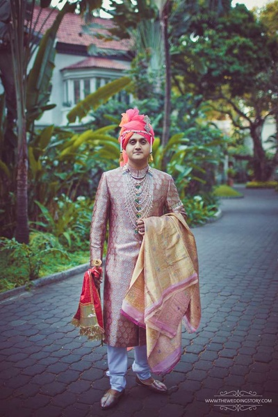 Groom Akshay in a silk peach Sherwani paired with a colorful safa and a green and white necklace