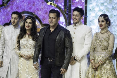 the bride and groom posing with Salman Khan at their reception