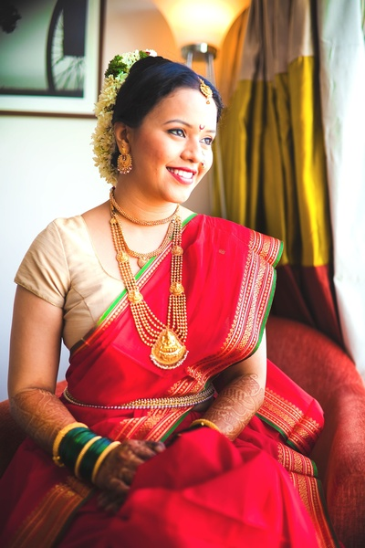 Classic vintage jewellery paired with a red Paithani silk saree. She is wearing a choker, necklace and Mohanmala with a pendant