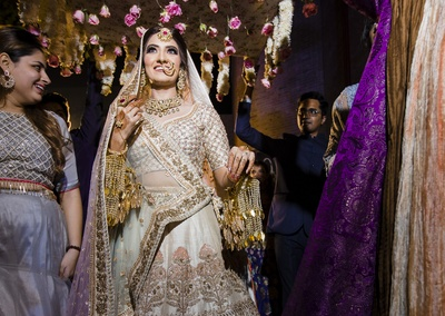 The bride is escorted by her family with a phoolon ki chaadar over her!