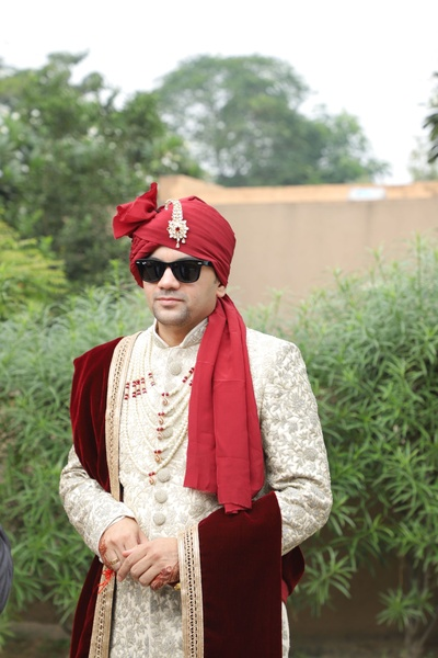 The groom looks dapper in an ivory fully embroidered sherwani paired with a maroon velvet dupatta and pearl jewellery.