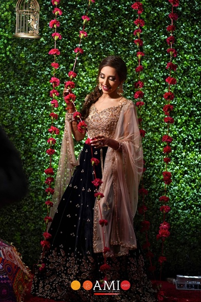 the bride posing against a floral background at her sangeet