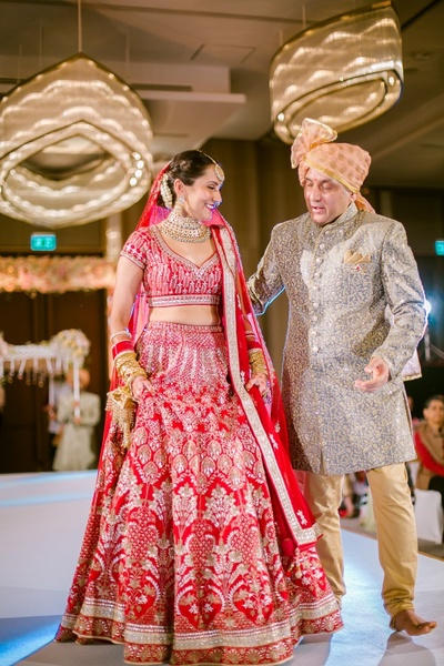 Bride and her father walk towards the mandap