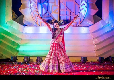 Purple and pink wedding lehenga embellished with kali like zari work and leheriya bordered hemline