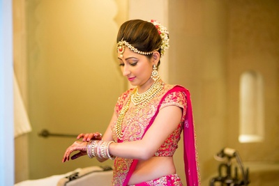 Pink bridal lehenga by Sabyasachi Mukherjee styled with polki studded necklace set and a gajra made with Mogra flowers