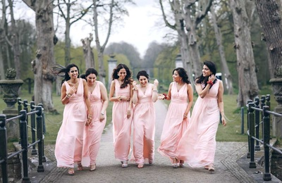 Bridesmaids in matching peach gowns for the wedding ceremony