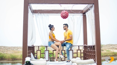Dressed in coordinated outfits for their pre wedding photo shoot by the beach in a cabana style setup