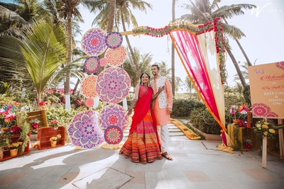 the bride and groom posing against a colourful backdrop