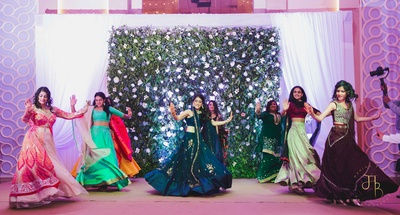 A candid capture of the bride and bridesmaids dancing at the sangeet ceremony