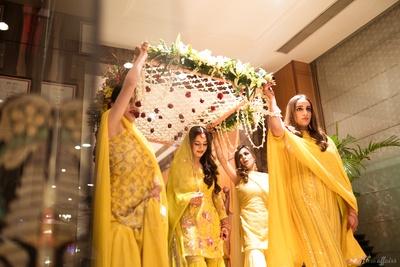 The bride entering the haldi ceremony venue in an elegant yellow sharara suit.