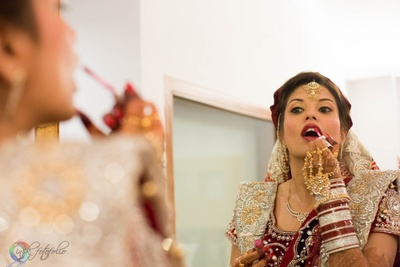 Getting ready for her most special day with touches of a deep maroon lipstick