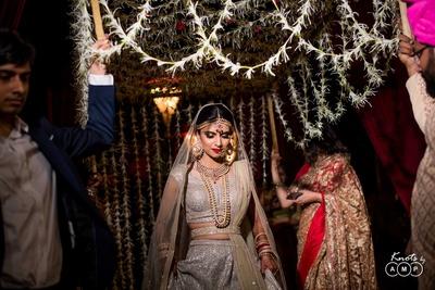 Bride enters the wedding mandap under the floral chaddar