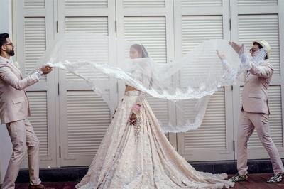The bride posing with designers Shivan & Naresh