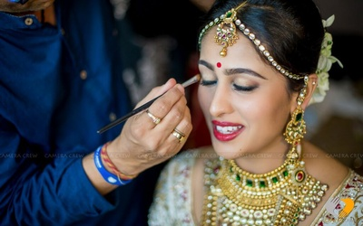 Bride in progress for her Big day. Decked in layers of jewellery she is looking breathtaking. Kundan-polki gold maathapatti and dangling earrings