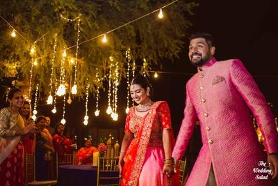 The bride flaunts a pink and orange heavily embellished lehenga, while the groom sports a bandhgala sherwani.