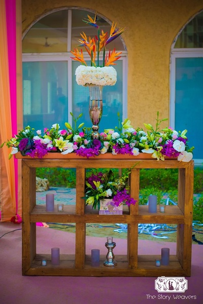 Decor props for the mehndi ceremony - a wooden structure holding fresh flowers and candles in hues of white, purple and green