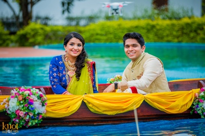 Wooden boat decorated with drapes and clustered floral arrangement for the couple's entry
