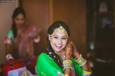 Bride Jeenal wearing green and yellow gota patti lehenga styled with gold jewellery and colorful bangles.