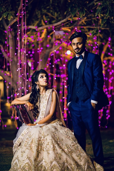 the cute couple posing in contrasting outfits at their engagement ceremony