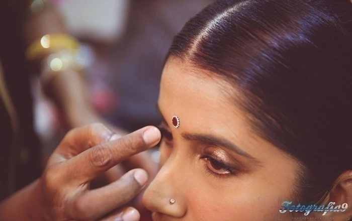 Applying kumkum/bindi/tilak on foreheads