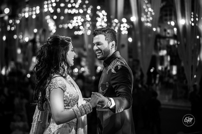 a black and white candid capture of the couple dancing at the sangeet