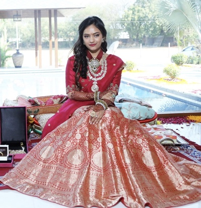 the bride in a red banrasi lehenga at a pre wedding function