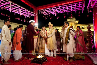 Wedding mandap lit up in hues of pink, decorated with dangling mudbells