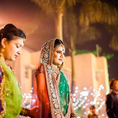 Coral and green wedding lehenga embellished with stones, beads and faux pearls