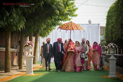 Bride enters royally with a phulkari printed umbrella.