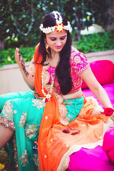 Bride Vasundhra wearing aqua blue lehenga paired with pink blouse and orange dupatta with  zari embroidery and minimal floral jewellery.