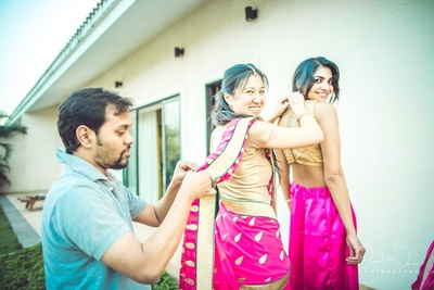 Brides maids getting ready in lovely bright pink Sarees for the wedding day.