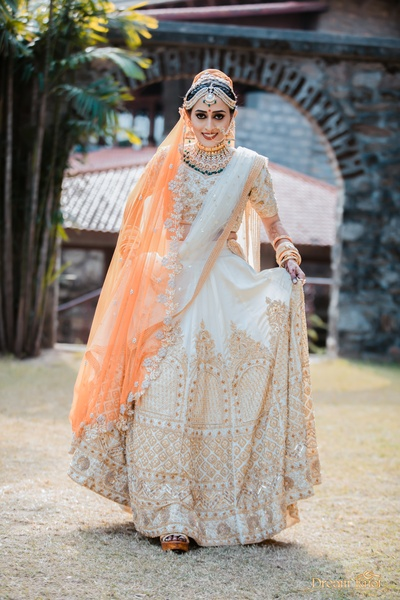 The bride looks nothing short of etheral in this ivory lehenga with dull gold embellishments!
