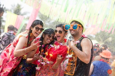quirky expressions, bright outfits, and funny props used in wedding rain dance party