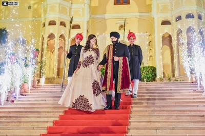 Bride and groom entering the reception ceremony held at Samode Palace, Jaipur.