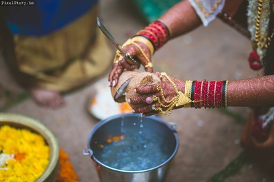 Megha breaking the coconut for a wedding ritual.