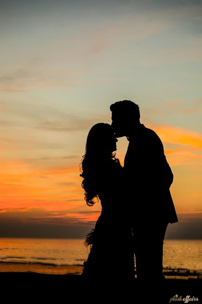 the bride and groom posing romantically at the engagement cum cocktail party against a stunning sunset backdrop