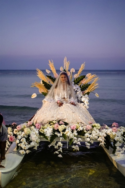 the bride entering in a boat decorated with flowers